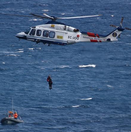Momento en el que la grúa del helicóptero sube al rescatador y el maniquí utilizado en el ejercicio. En la parte inferior, la lancha de Protección civil de Blanes / Foto: Anna Sais