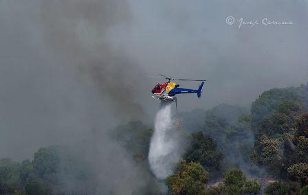 Un helicóptero equipado con un deposito ventral descarga agua en el incendio / Foto: Josep Carmona