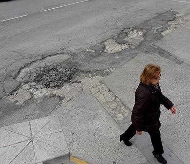 Una mujer camina junto al socavón de la calle Lluís Companys / Foto: JFG