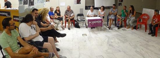 A mitad de la reunión, una persona colocó en la mesa del coordinador de la reunión un cartel de Podemos / Foto: JFG