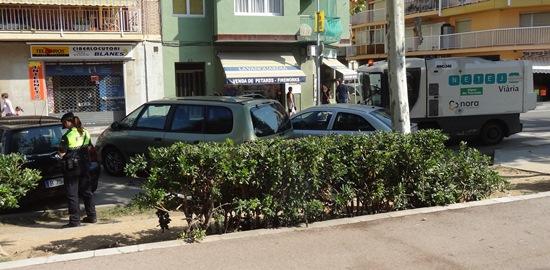 Una agente multa un turismo, mientras un vehículo de Nora limpia con dificultad la calzada, ayer en la Avenida Catalunya / Foto: JFG