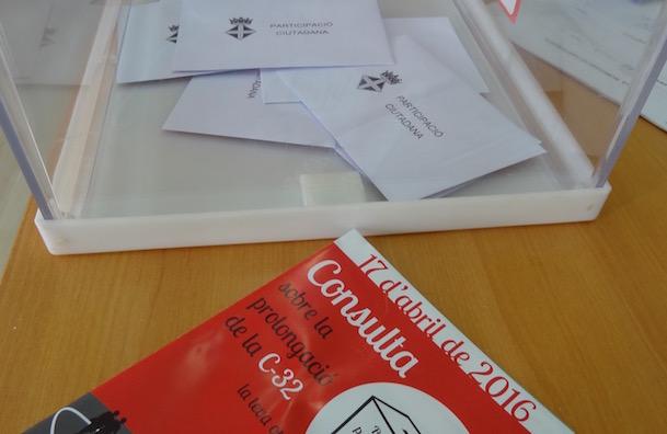 Vots en una urna i follet informatiu